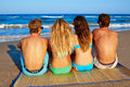 Friends group couples sitting in beach sand rear view back looking to the sea Stock Photography