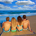 Friends group couples sitting in beach sand rear view back looking to the sea Royalty Free Stock Photos