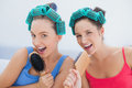 Friends in hair rollers singing into their hairbrushes Royalty Free Stock Photo