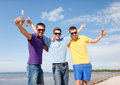 Friends having fun on beach with bottles of beer summer holidays vacation happy people concept group the or non alcoholic Royalty Free Stock Image