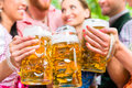 Friends having fun in beer garden while clinking glasses