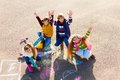 Friends having fun with chalk group of four boys and girls in autumn clothes painting on the asphalt lifting hands smile on theirs Stock Image