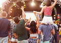 Friends having fun in the crowd at music festival, back view Royalty Free Stock Photo