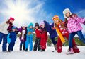 Friends having fun in snow group of happy kids on day holding hands laughing and smiling Royalty Free Stock Photos