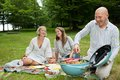 Friends having meal at an outdoor picnic happy caucasian cooking barbeque in forest park Royalty Free Stock Photos