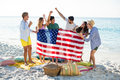 Friends holding American flag on shore at beach Royalty Free Stock Photo
