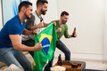Friends holding a brazilian flag profile view of group of male drinking beer and watching the brazil olympics at home Royalty Free Stock Photography