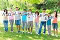 Friends holding placards spelling volunteer full length of on campus Royalty Free Stock Photo