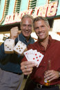 Friends Holding Playing Cards And Dices Against Casino Stock Photos