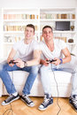 Friends at home playing video game sitting on couch holding controllers Stock Image