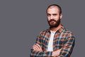 In friends with irony handsome young bearded man keeping arms crossed and expressing ironic smile while standing against grey Stock Photos