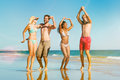 Friends jumping on ocean beach in vacation four men and women the having lots of fun their the water Royalty Free Stock Photo