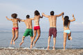 Friends jumping into the sea rearview of holding hands Stock Photo