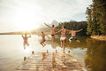 Friends jumping into the water from a jetty portrait of young young people having fun at lake on summer day Stock Photos