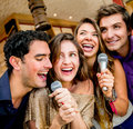 Friends karaoke singing group of at the bar Stock Images