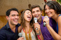 Friends karaoke singing group of having fun at the bar Royalty Free Stock Images
