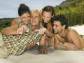 Friends looking at pictures on the beach Stock Photography