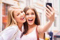 Friends making selfie two beautiful young women and grimacing Stock Photo