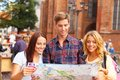 Friends with map three tourist outdoors Royalty Free Stock Images