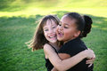 Friends multi cultural hugging at the park Royalty Free Stock Photos