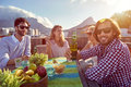 Friends party gathering on rooftop group of sitting hanging out with drinks the Royalty Free Stock Photos