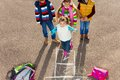 Friends play hopscotch group of three kids playing game with girl jumping Stock Photo