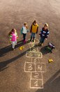Friends play outside on hopscotch group of kids jumping the game drawn the asphalt after school wearing autumn clothes after Stock Image