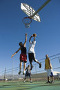 Friends playing basketball against blue sky low angle view of multiethnic clear Royalty Free Stock Photos