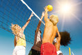 Friends playing beach volleyball players doing summer sports trying to block a dangerous attack in a game Stock Image