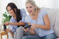 Friends playing video games and having fun at home on couch Royalty Free Stock Photos