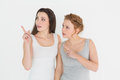 Friends pointing away against white background two young female Royalty Free Stock Image