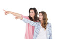 Friends pointing away against white background two young female Royalty Free Stock Images