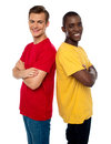 Friends posing back to back with arms crossed Royalty Free Stock Photo