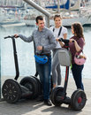 Friends posing near segways on shore