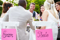 Friends proposing champagne toast at wedding sitting outside around table Royalty Free Stock Photo
