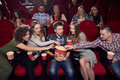 stock image of  Friends pulling hands to popcorn of one shocked boy in center.