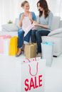 Friends with purchase and shopping bag on foreground sitting the sofa Royalty Free Stock Photos
