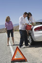Friends Refueling Car With Warning Triangle In The Foreground Royalty Free Stock Image