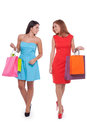 Friends shopping full length of two beautiful young women holding bags and smiling Stock Images