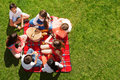 Friends sitting near picnic basket on green meadow Royalty Free Stock Photo