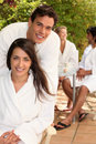 Friends sitting on a terrace couple with in toweling robes Royalty Free Stock Photos
