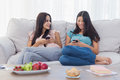 Friends sitting using their smartphones on the couch at home Royalty Free Stock Photos