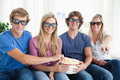 Friends smiling as they eat popcorn and watch a 3d movie Stock Photography