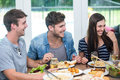 Friends smiling while having meal at table young in house Stock Photography