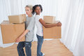 Friends standing back to back holding moving boxes in their new home Stock Photo