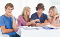 Friends studying as one guy looks at the camera Royalty Free Stock Photography