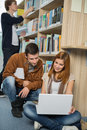 Friends studying together on laptop in library young college Royalty Free Stock Photo
