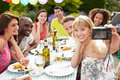 Friends taking self portrait on camera at outdoor barbeque sitting down table smiling Royalty Free Stock Photography