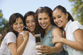 Friends taking self portrait through mobilephone in park happy female Royalty Free Stock Photos