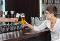 Friends toasting as they enjoy a pint of beer two male together sitting at the counter in bar or nightclub Royalty Free Stock Photos